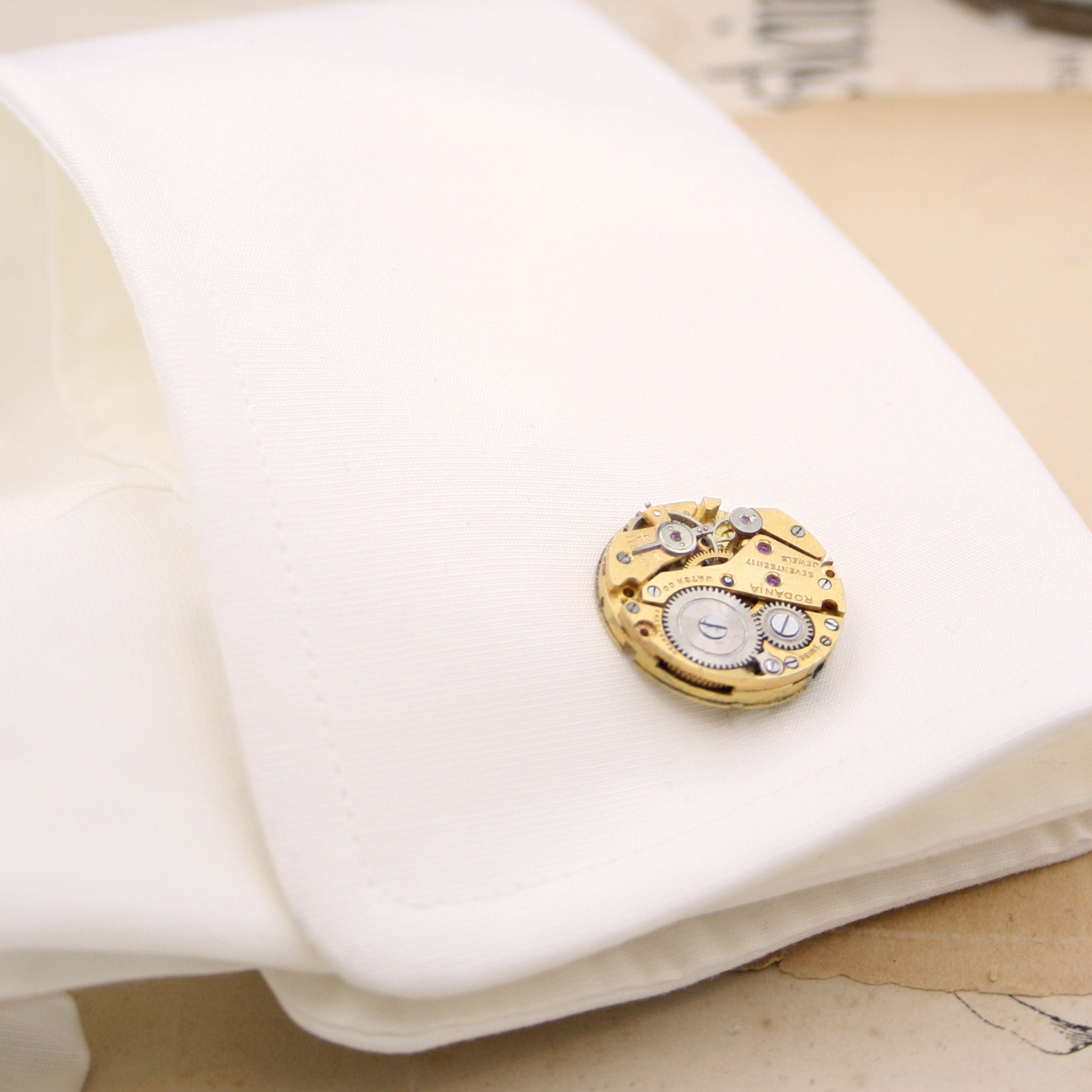 gold steampunk cufflinks featuring antique watch movements in a shift cuff