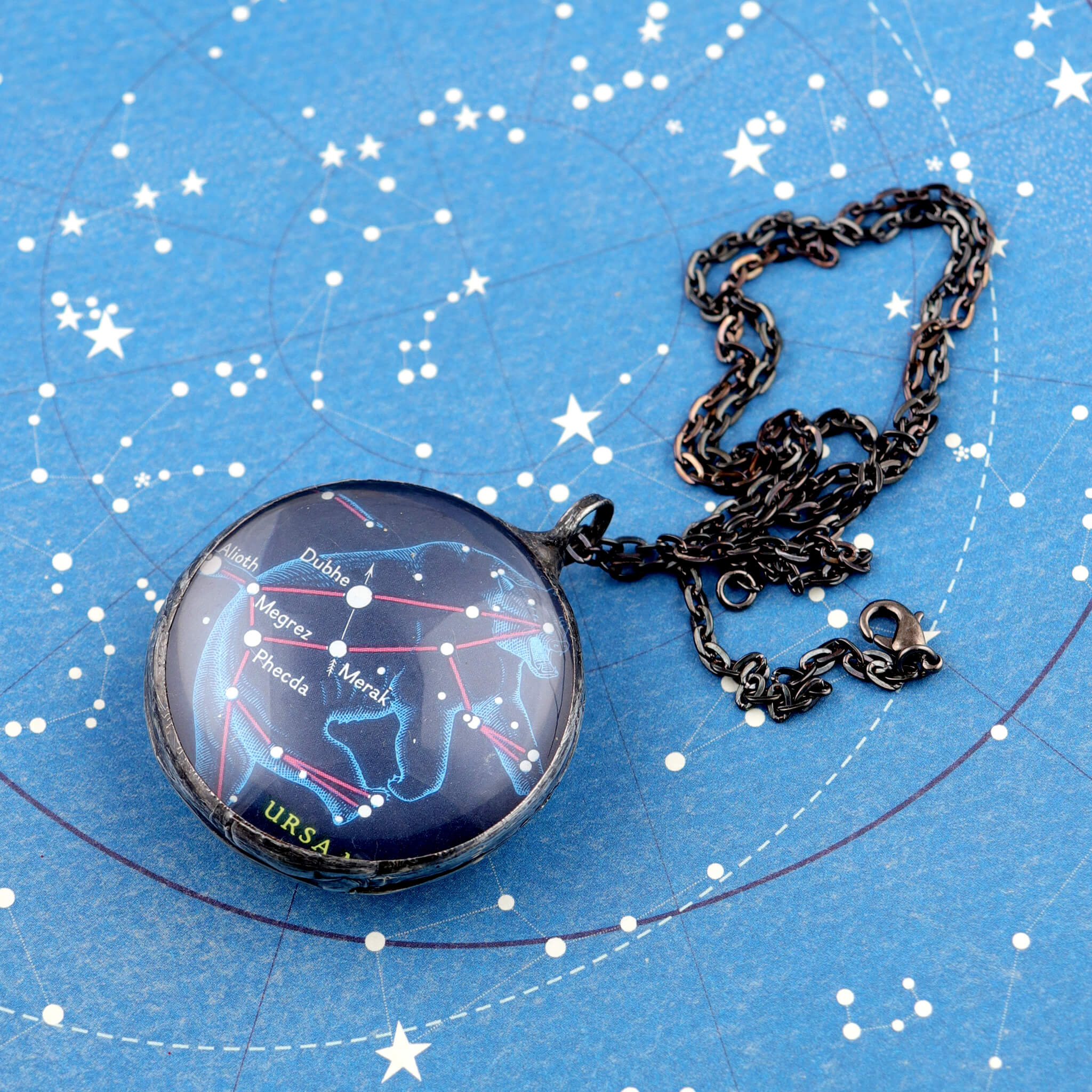 Ursa Major stained glass necklace lying on celestial stationery