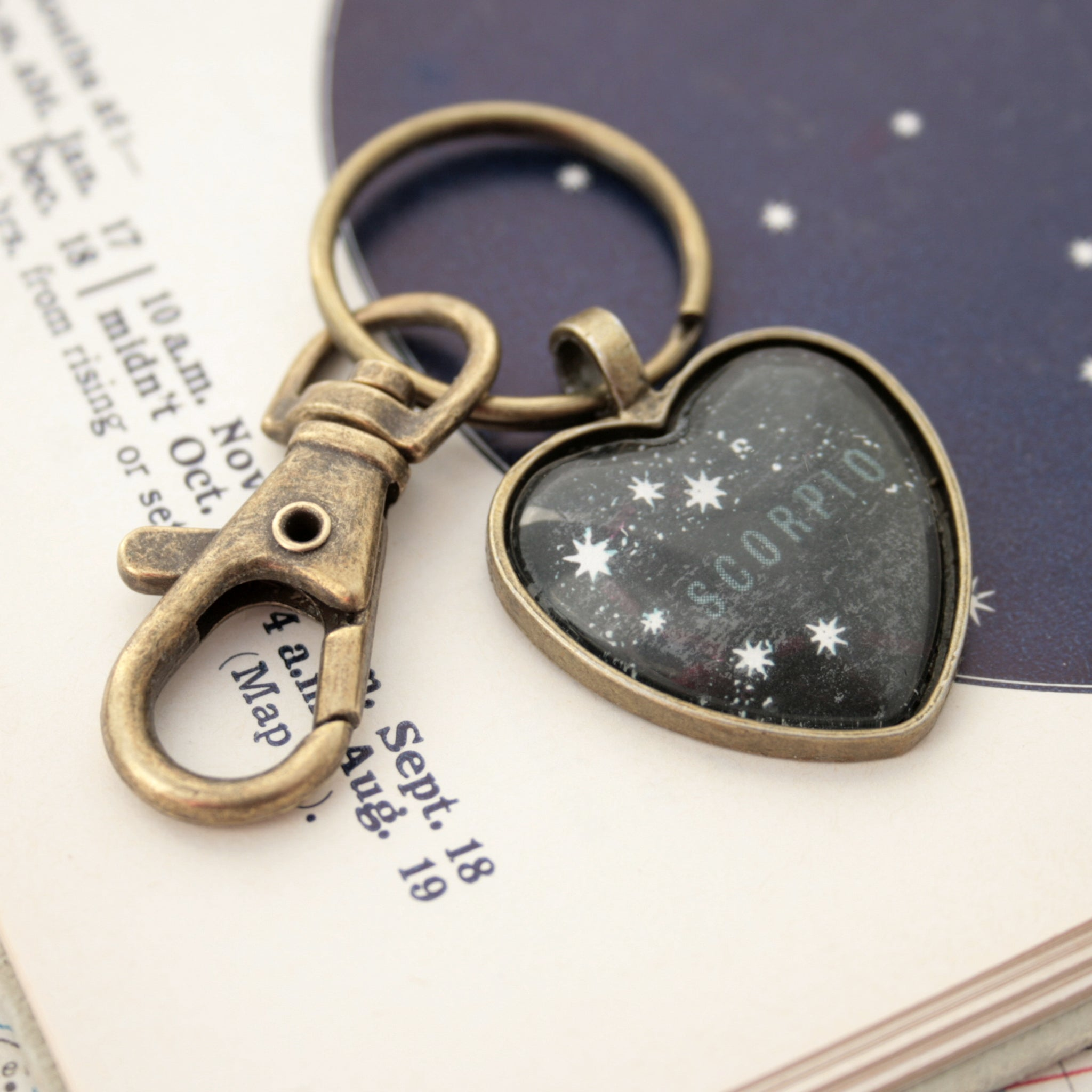 Heart shaped keychain featuring scorpio zodiac on black map