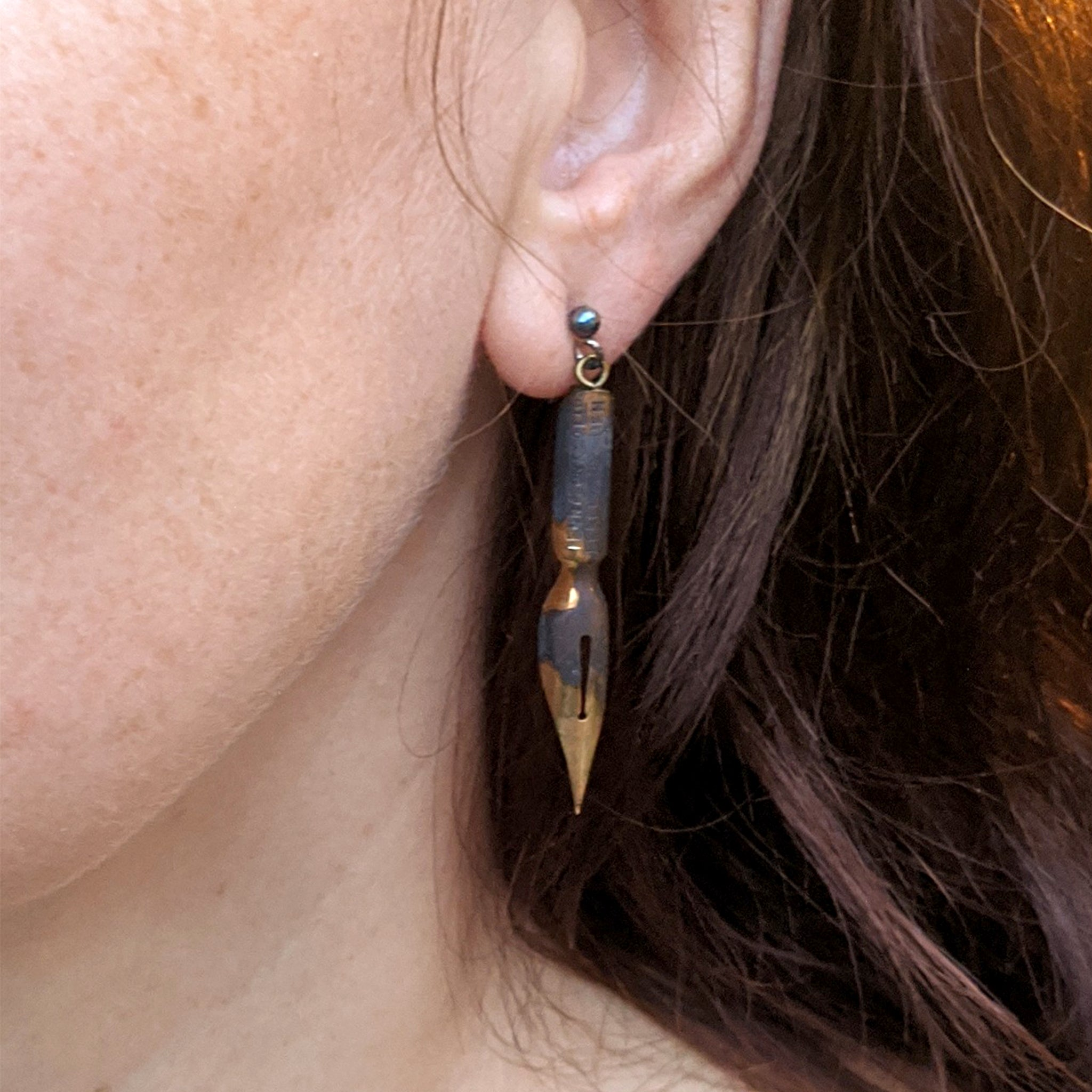 Long Dangle Earrings made of antique pen nibs in gold color worn on ear