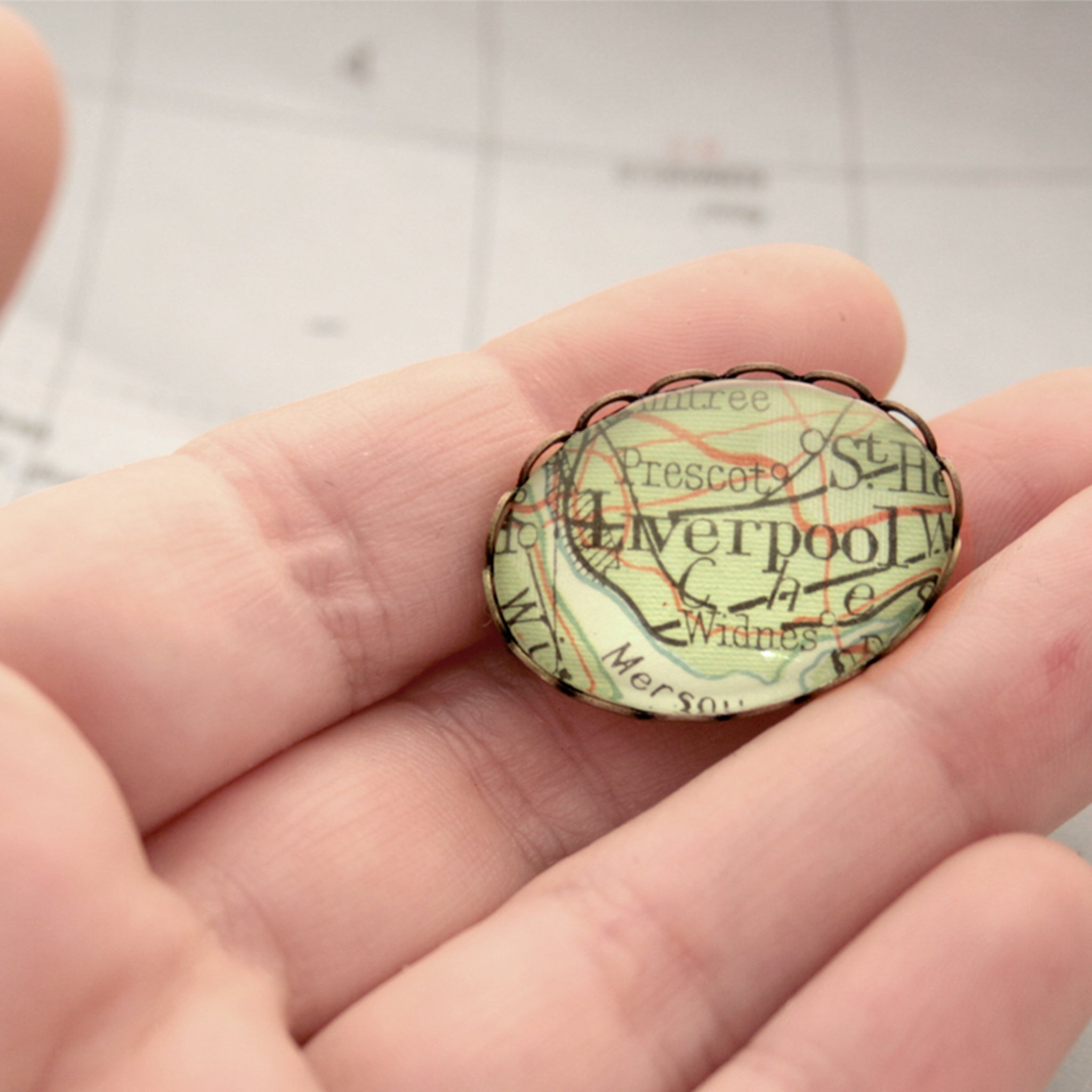 Antique Bronze brooch featuring map of Liverpool lying on hand