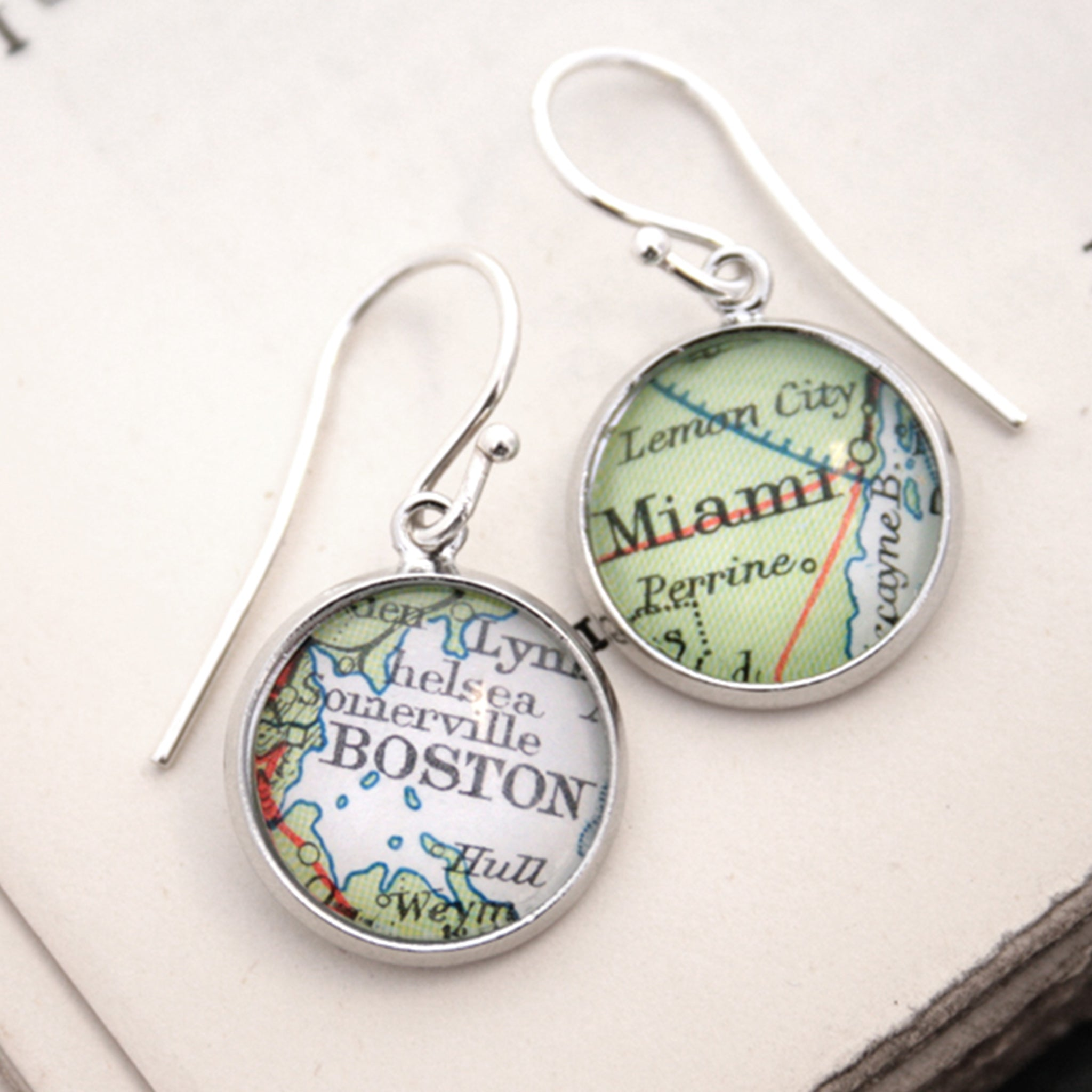 silver dangle earrings featuring maps of Boston and Miami