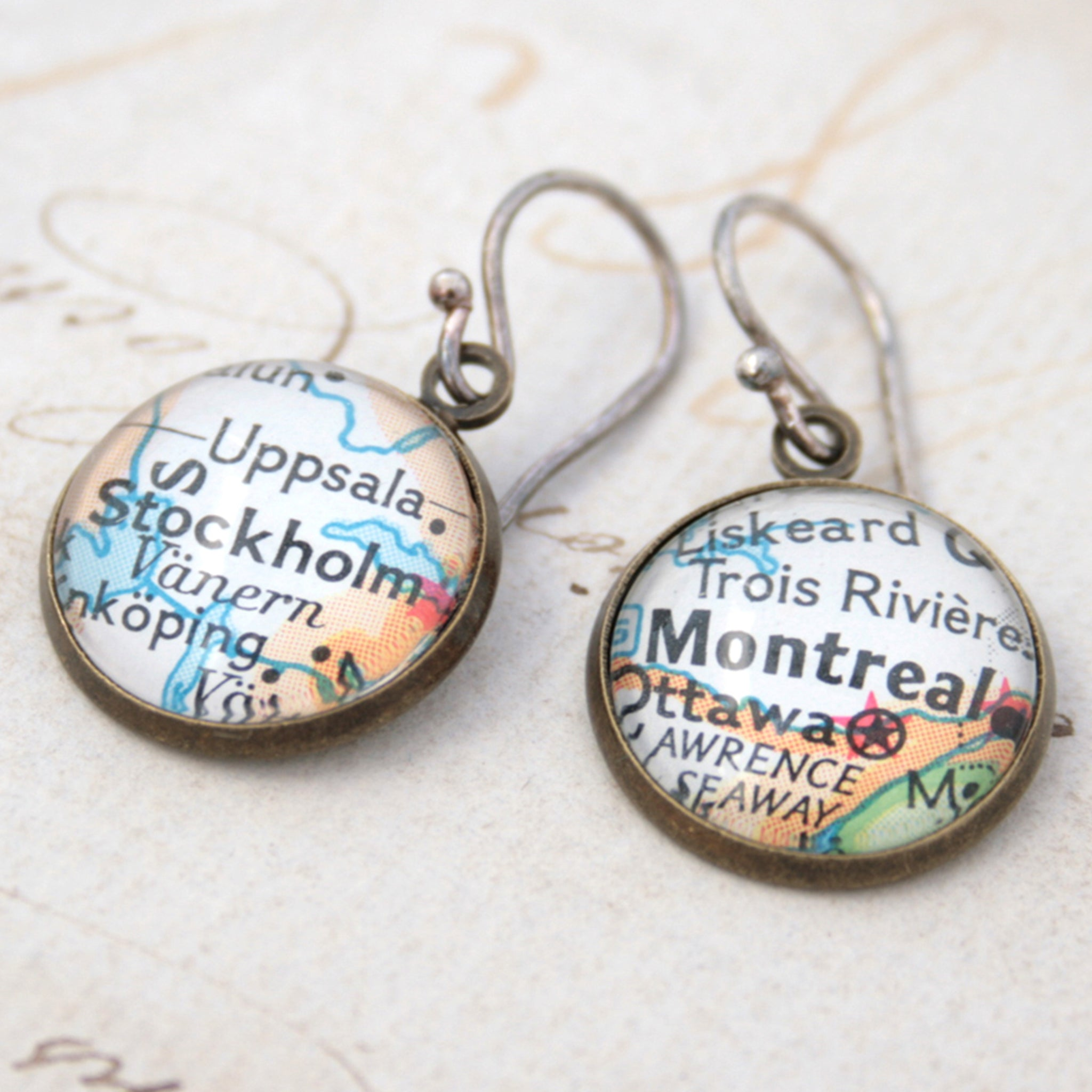 Bronze dangle earrings featuring maps of Stockholm and Montreal