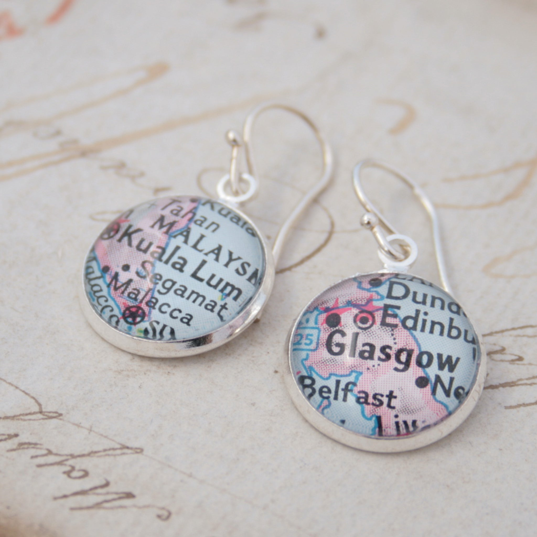 silver dangle earrings featuring maps of Glasgow and Kuala Lumpur