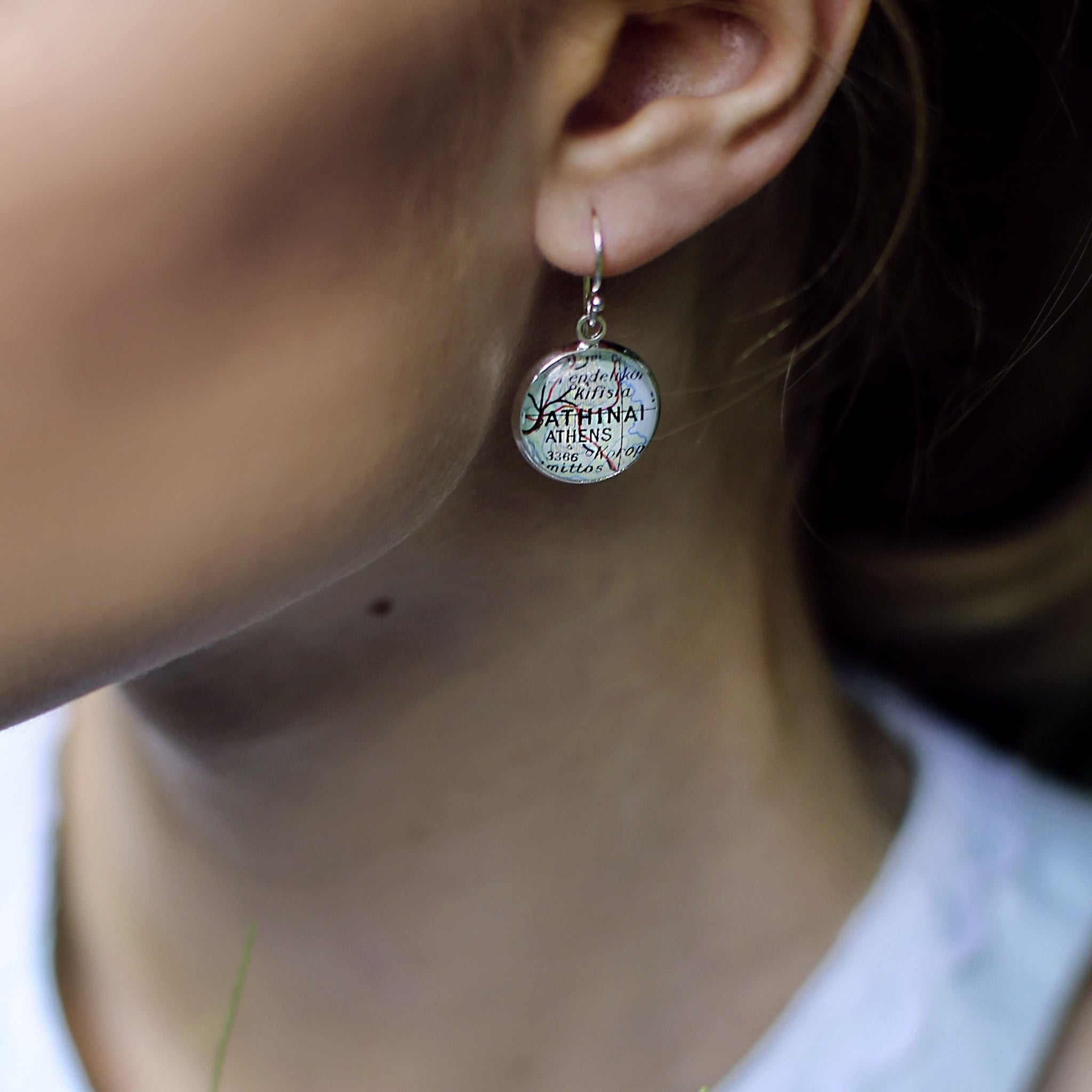 Model wearing silver dangle earrings featuring maps of Athens