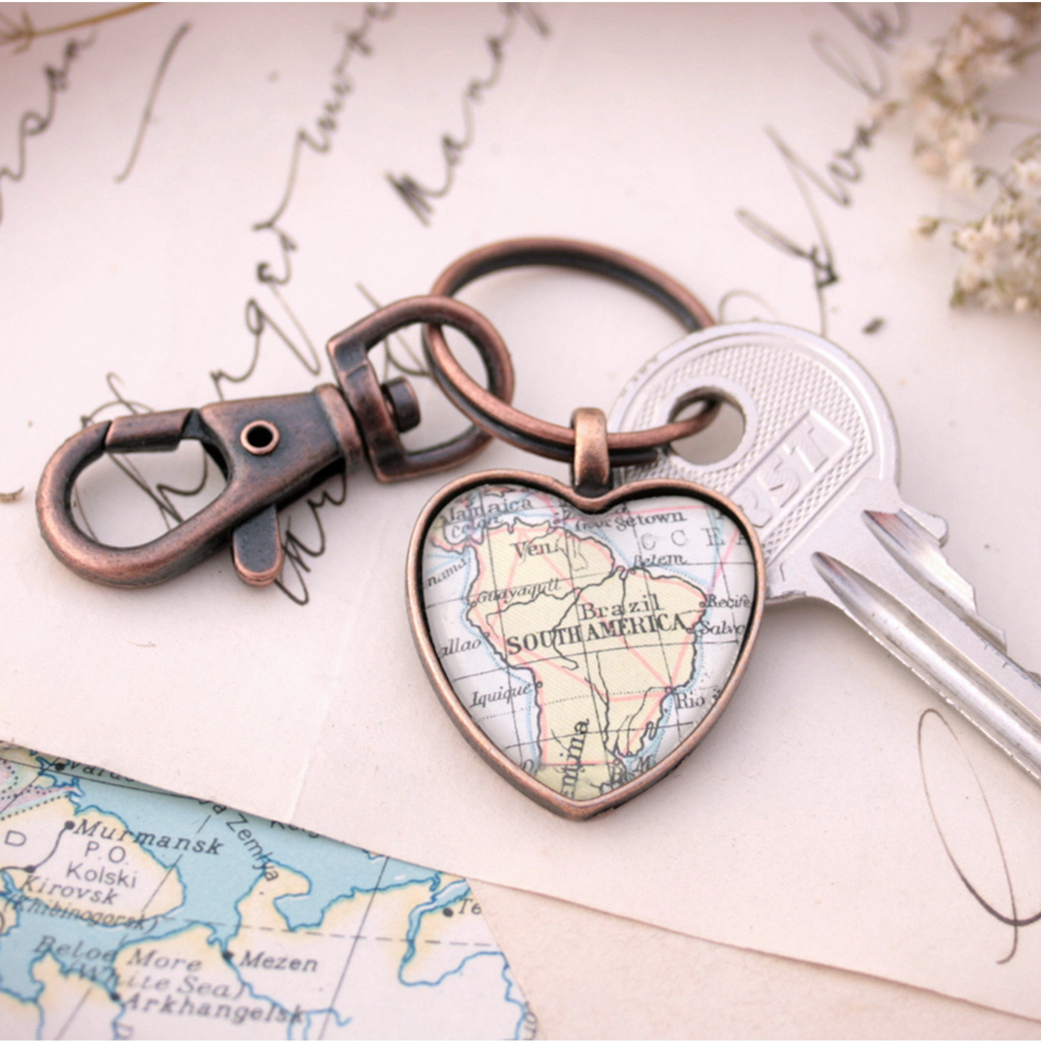 Heart shaped keychain in copper tone featuring map of South America