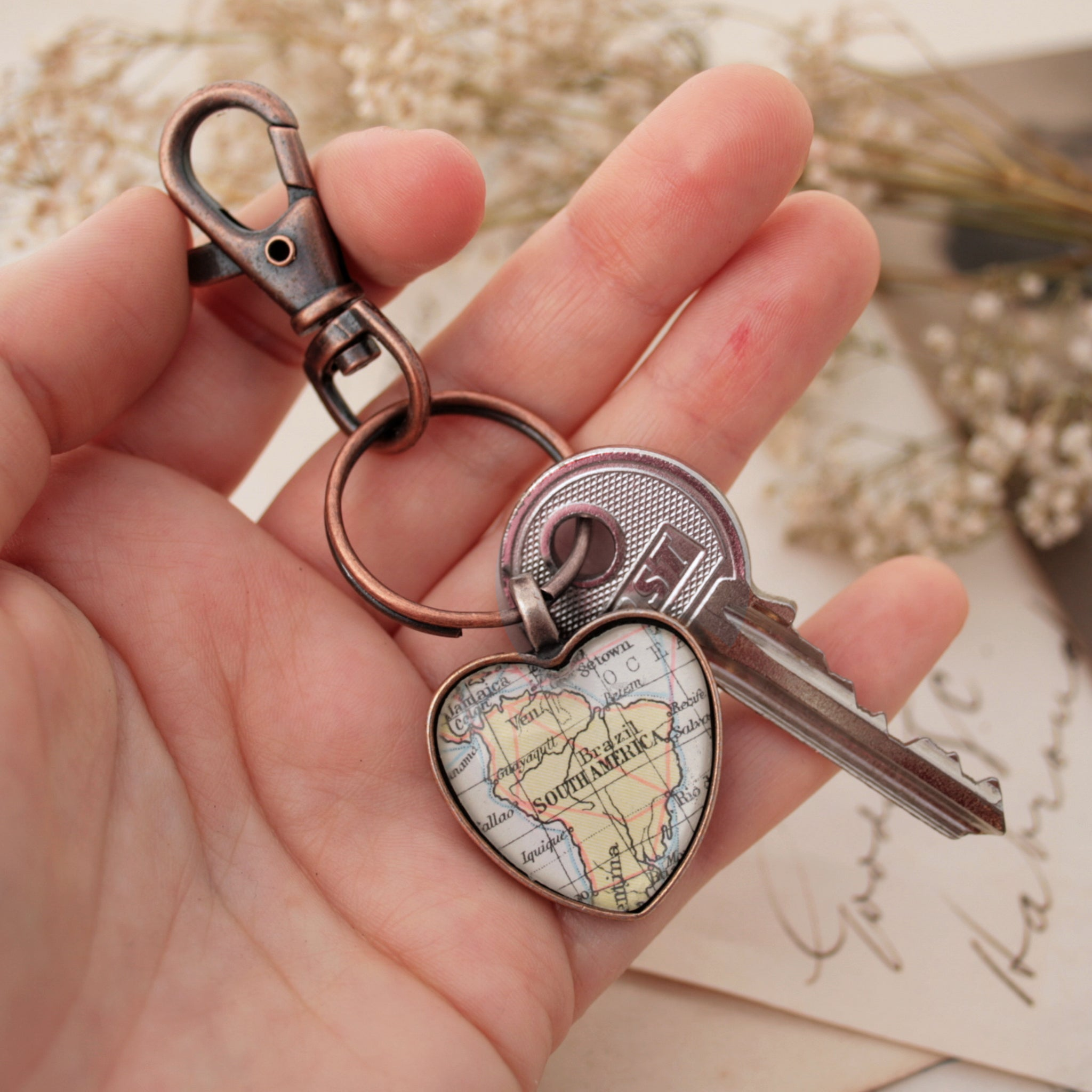 Hold in hand Heart shaped keychain in copper tone featuring map of South America