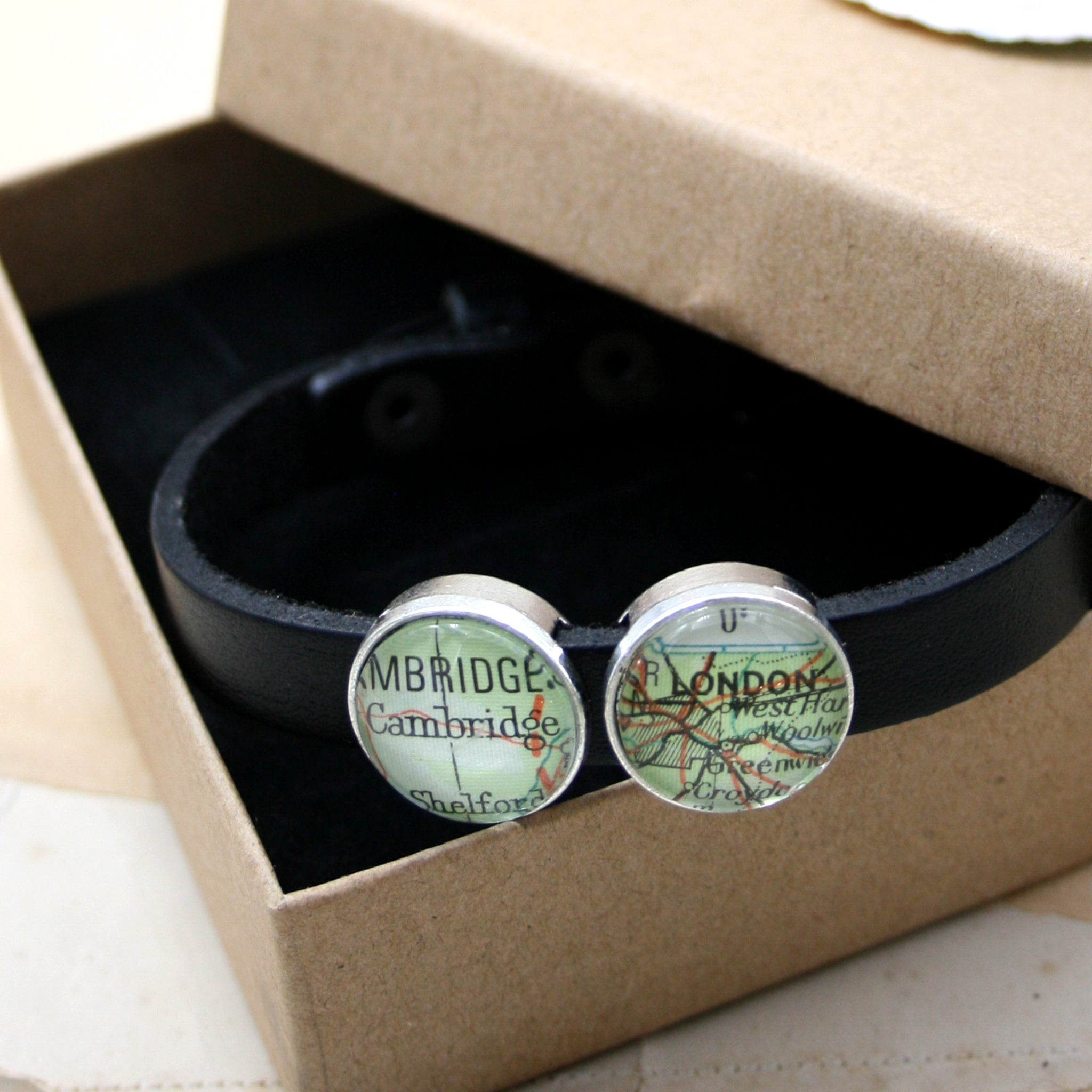 Black leather bracelet featuring map locations in a box