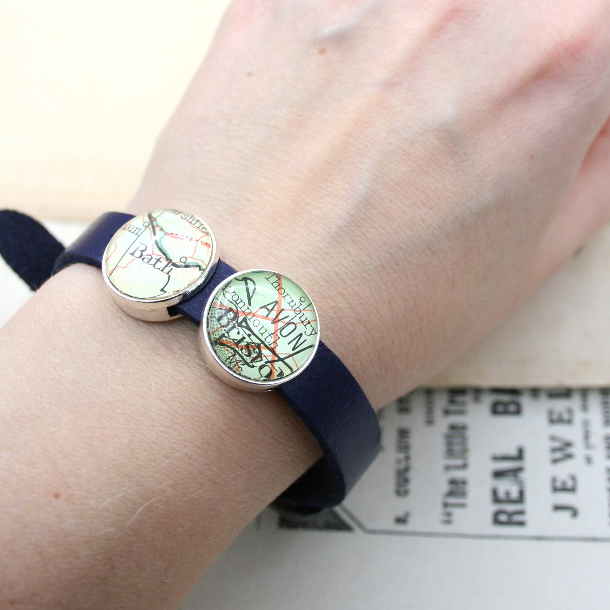 Worn on hand blue leather bracelet featuring map locations