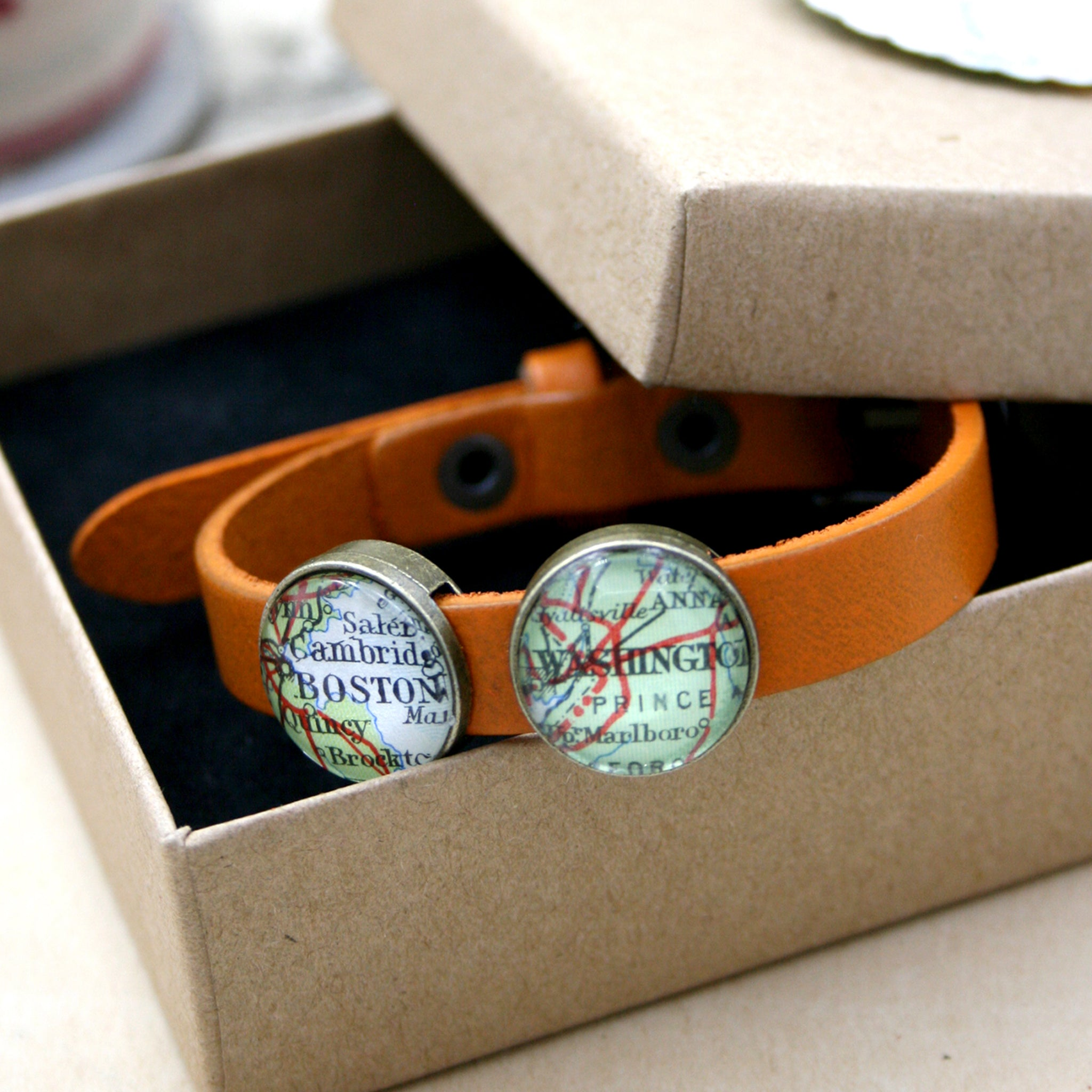 Orange leather bracelet featuring map locations in a box