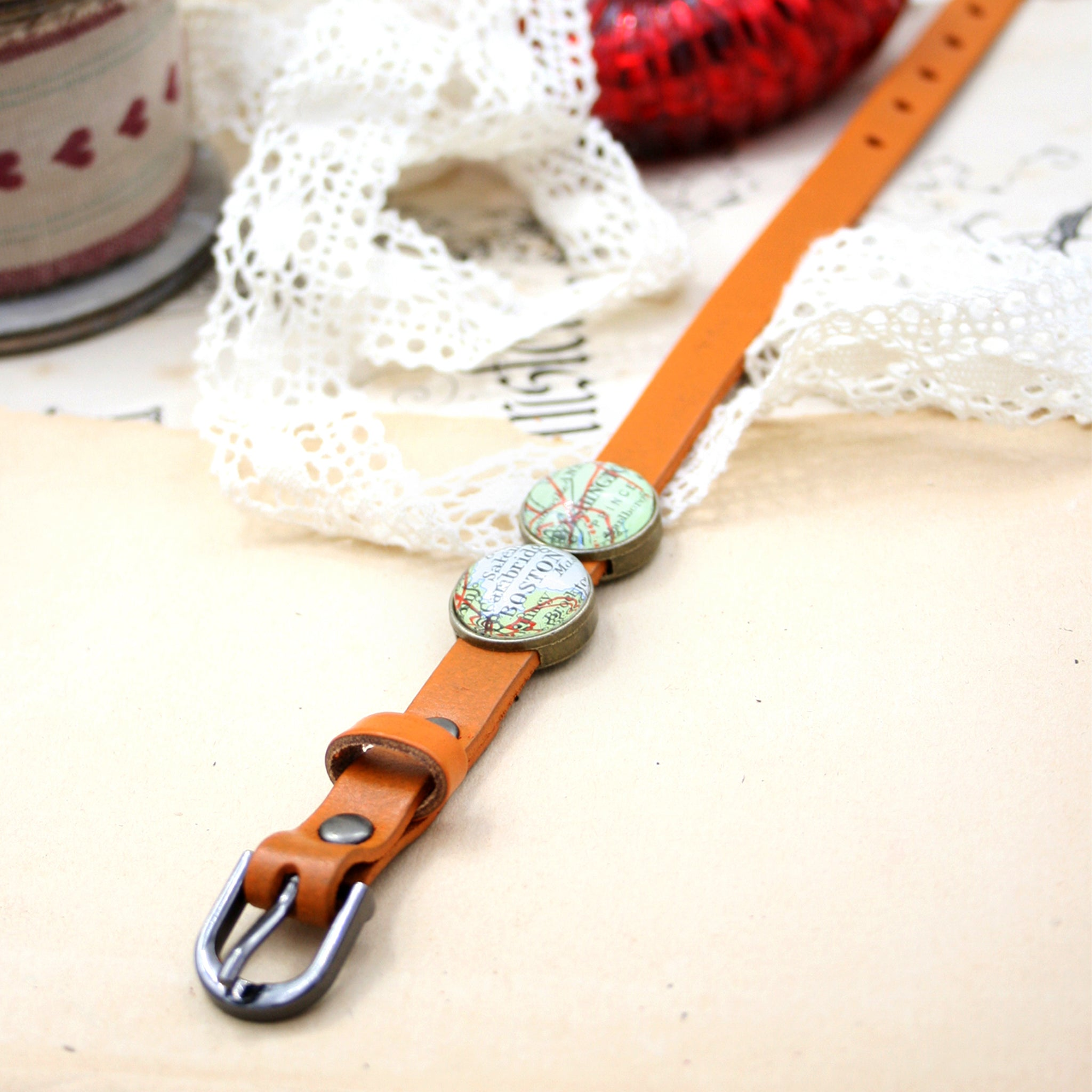 Orange leather bracelet featuring map locations