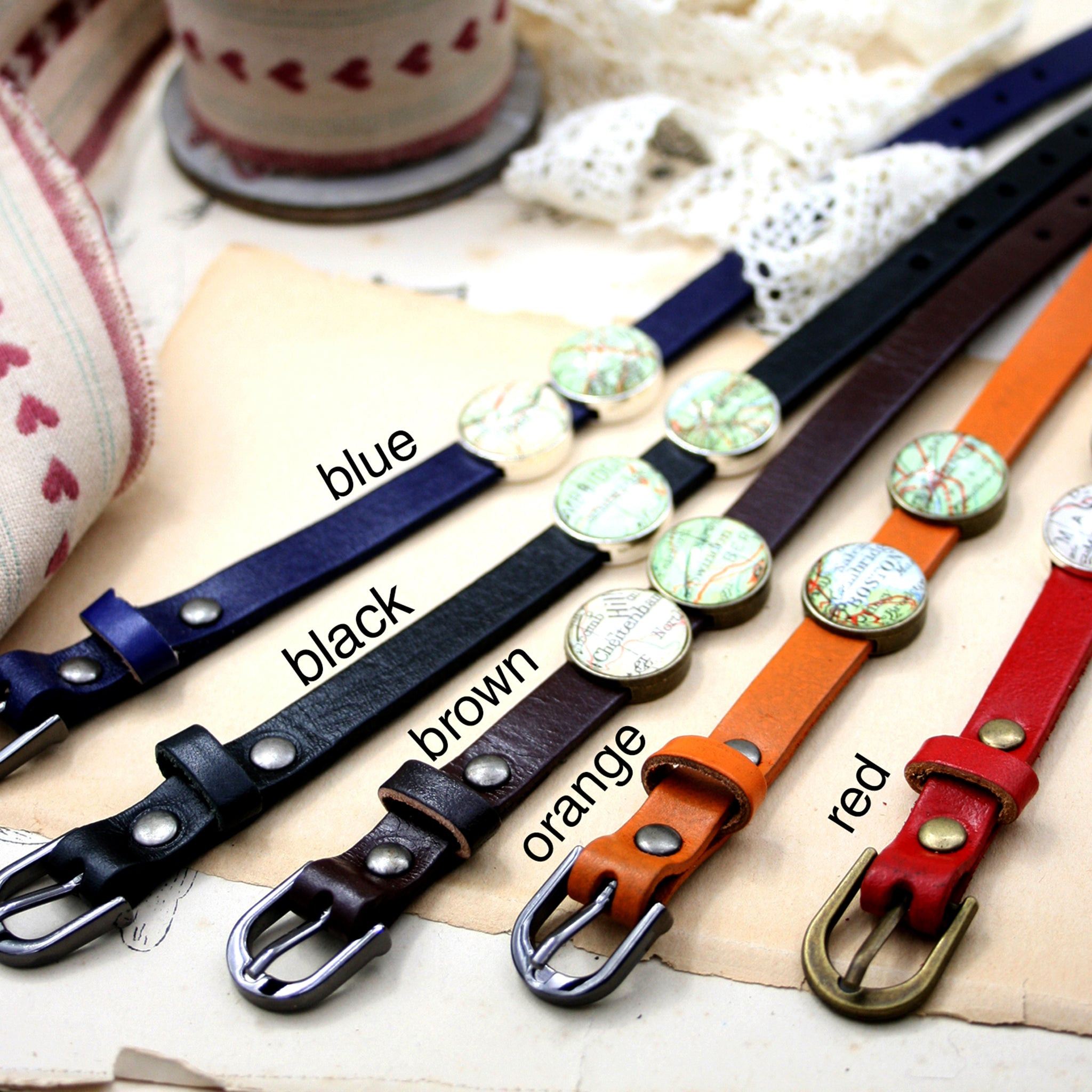 Blue, black, brown, red and orange leather bracelets featuring map locations