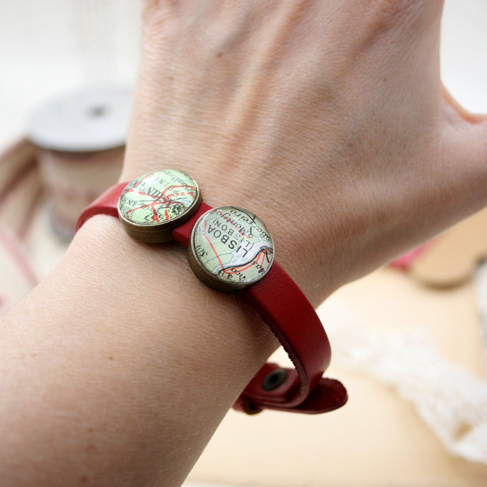 Worn on hand red leather bracelet featuring map locations