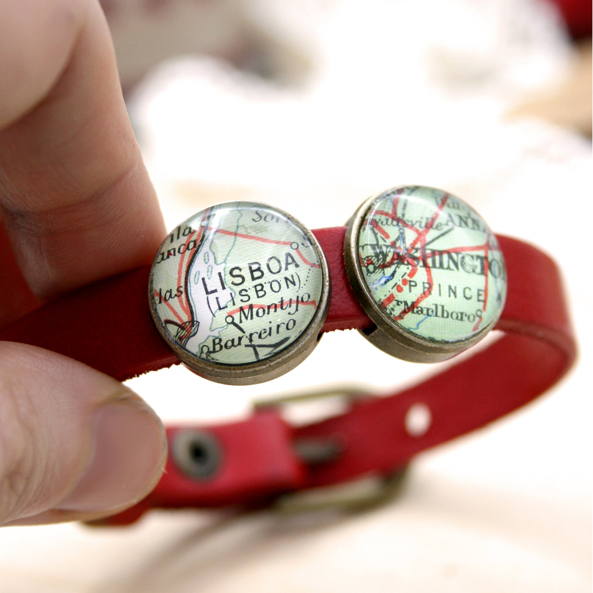 Hold in hand red leather bracelet featuring map locations