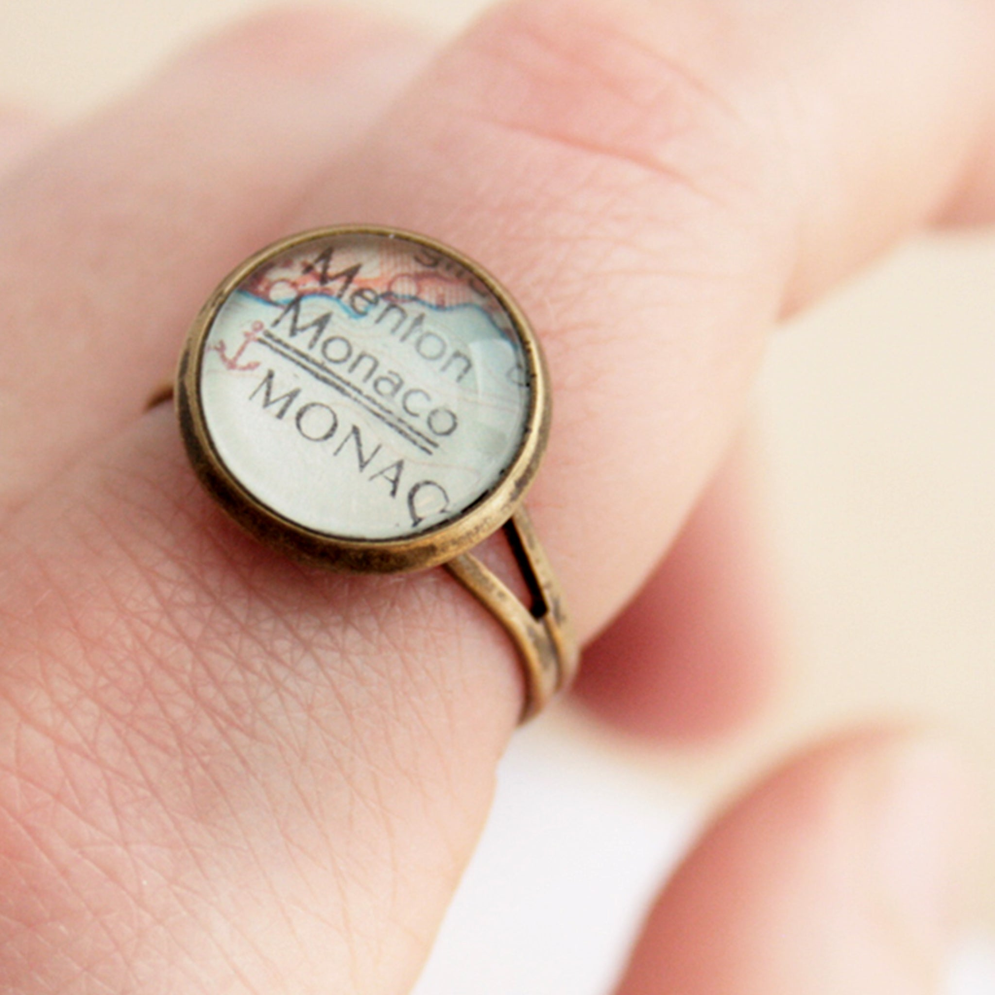tiny wanderlust ring in antique bronze tone personalised with map of Monaco worn on hand
