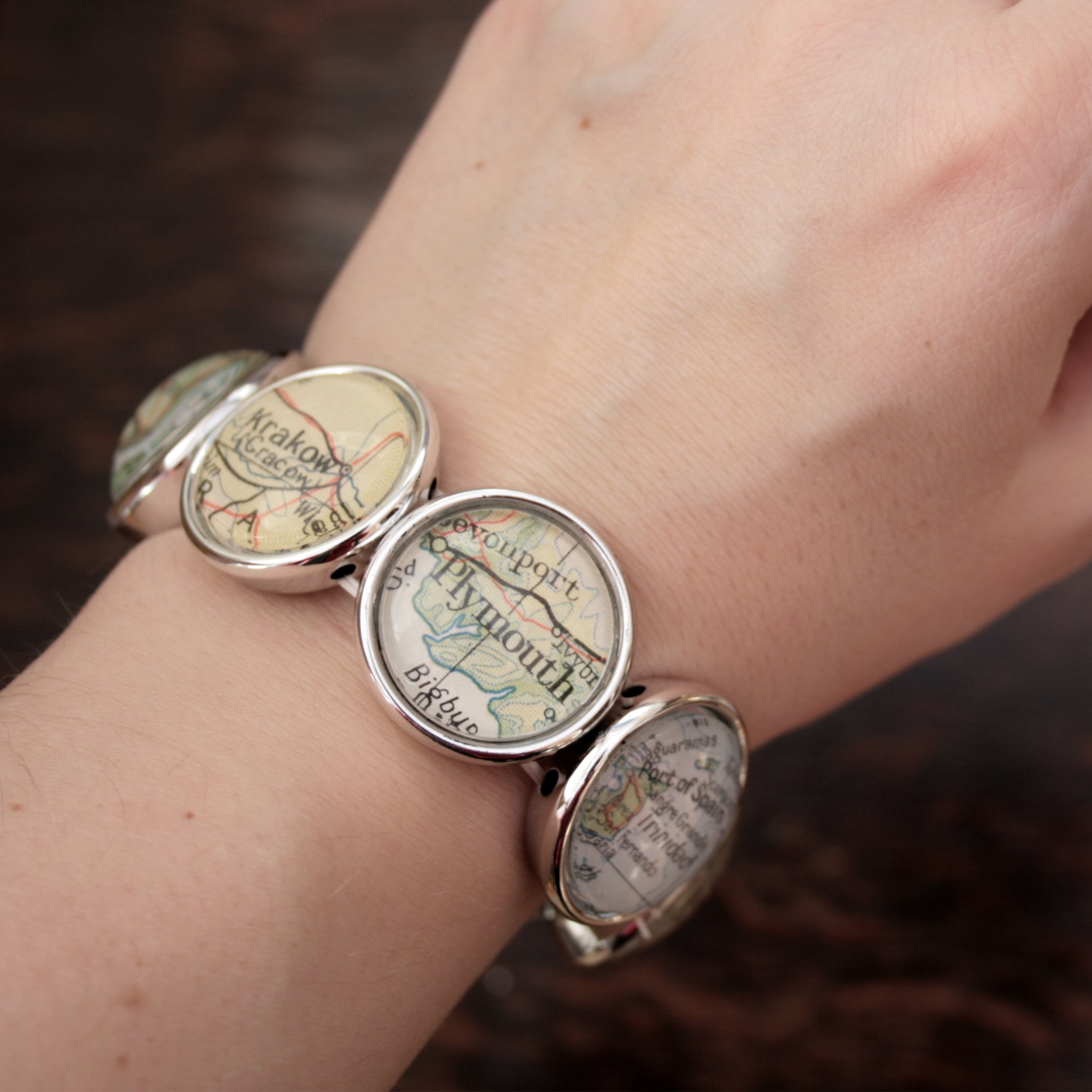 Worn on hand Stretchy bracelet in silver tone featuring custom map locations