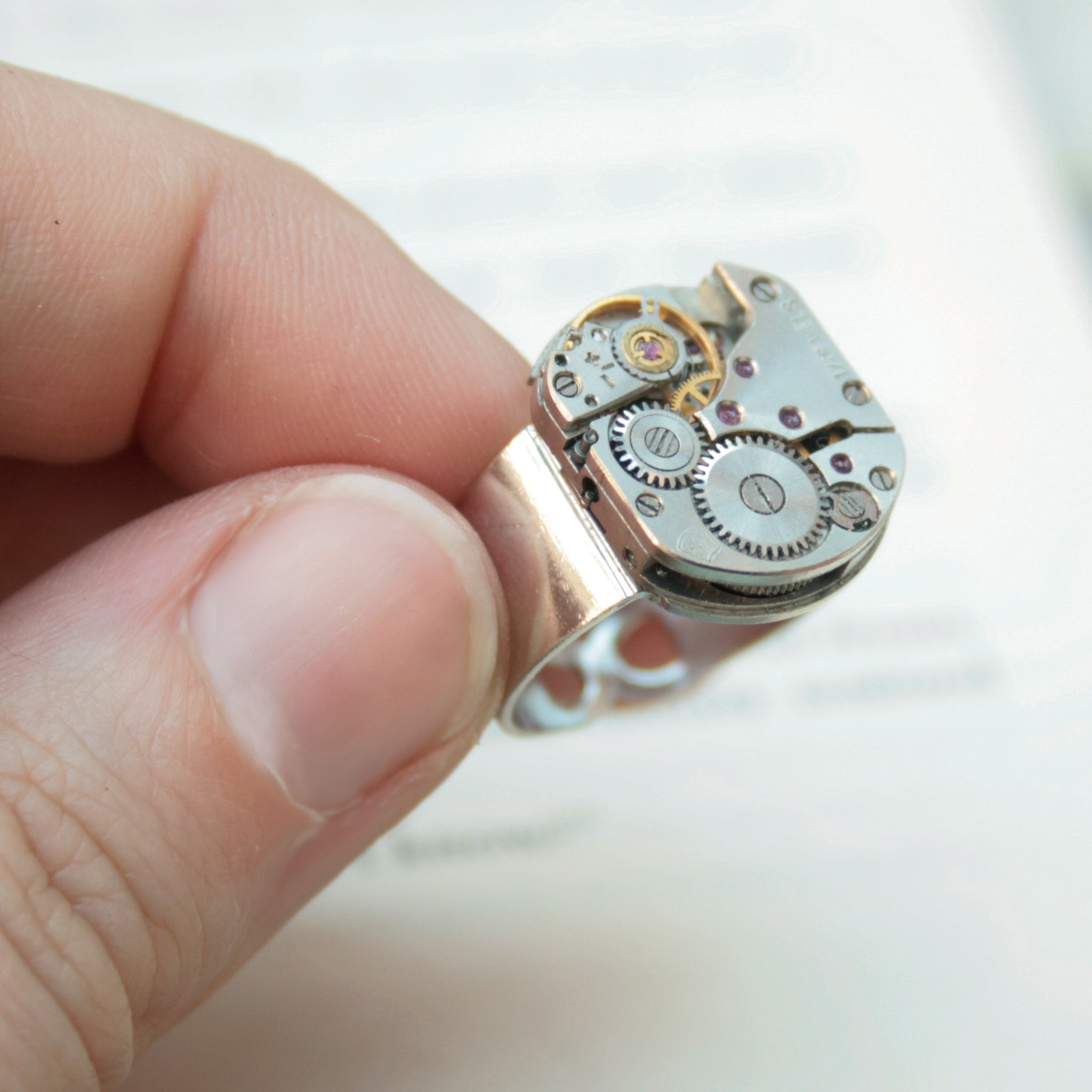 Mens Pinky Ring in Steampunk Style made of watch movement in silver color being hold in hand