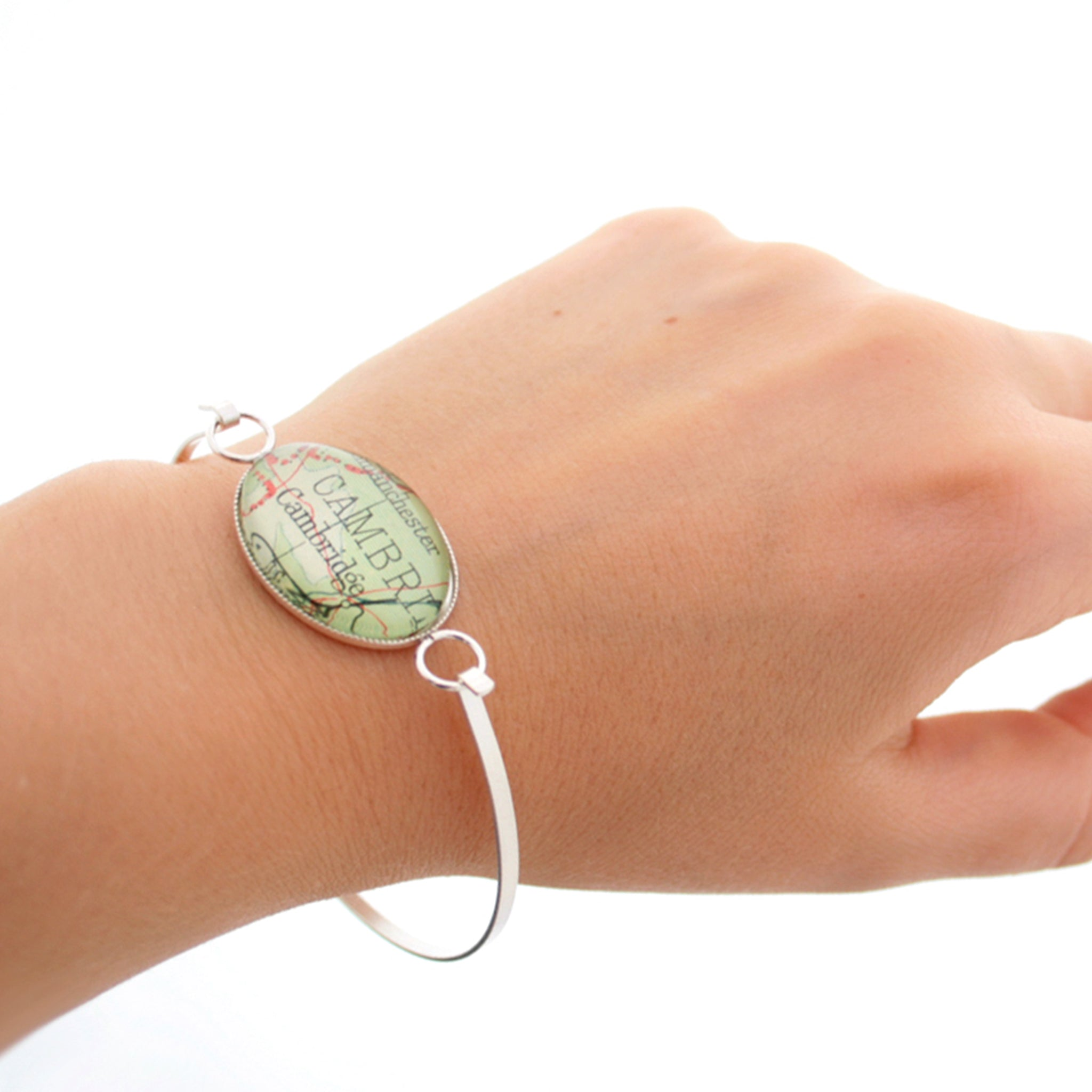 Sterling silver bangle bracelet featuring map of Cambridge worn on hand