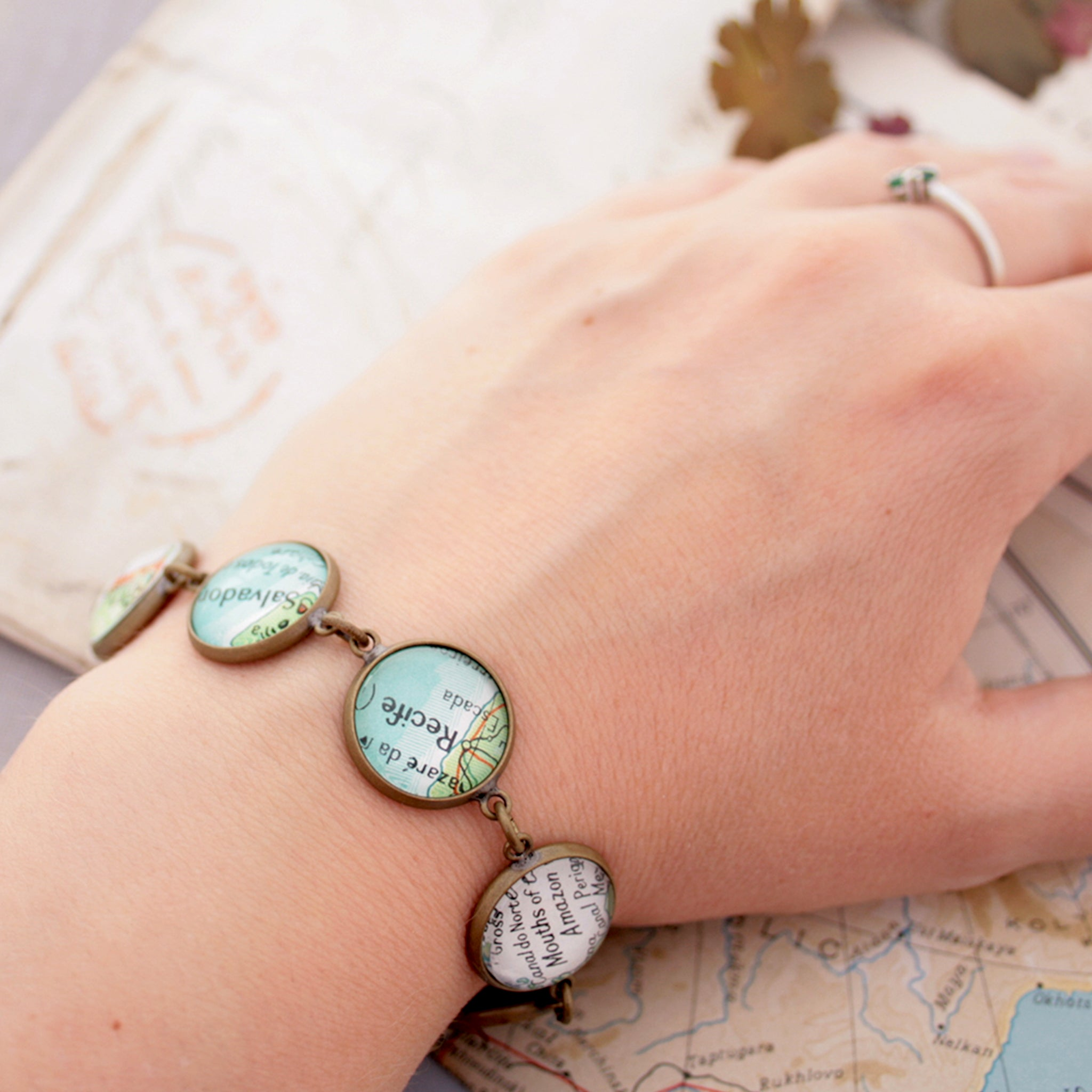 Worn on hand Antique bronze beaded bracelet featuring different map locations