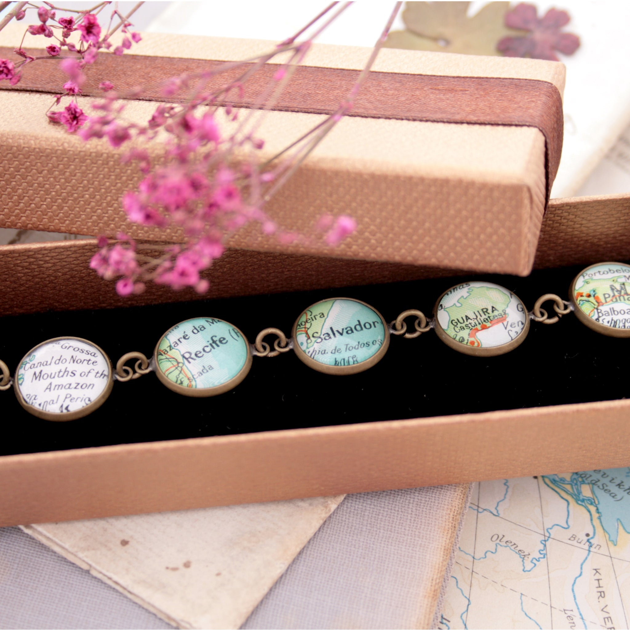 Antique bronze beaded bracelet featuring different map locations in a brown box