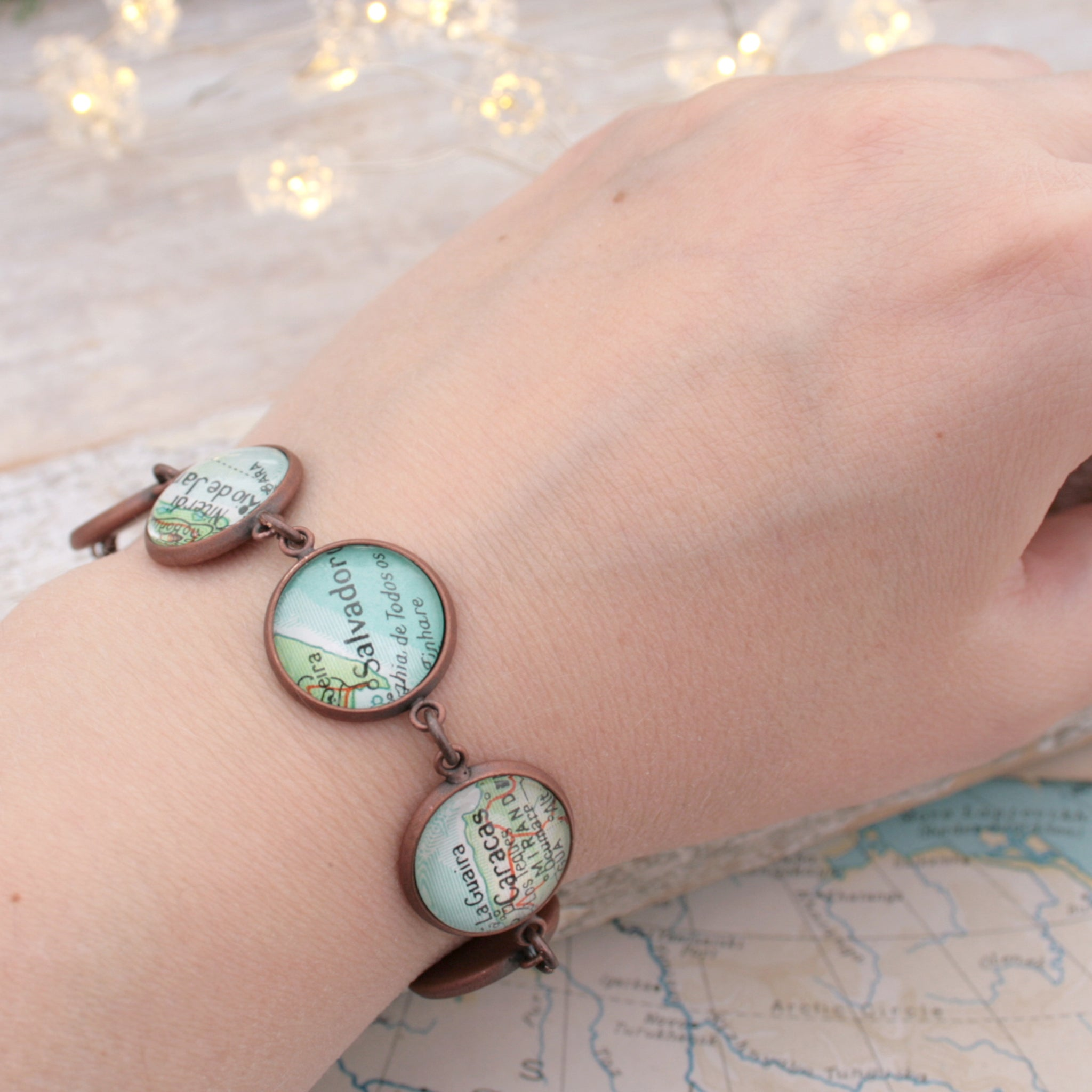 Worn on hand antique copper beaded bracelet featuring different map locations