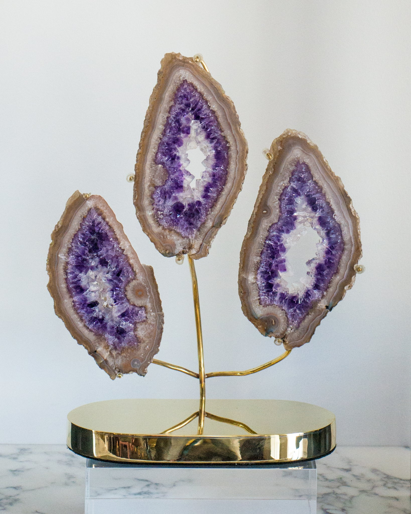 A sculpture of 3 Amethyst slices attached to a custom Studio Maison Nurita brass base. Amethyst is a remarkable stone of spirituality and contentment, it stills the mind and enhances a meditative state. This objet will add a touch of drama to any space.