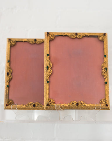 An antique gold picture frame with filigree work and jewels backed in pink silk moiré.