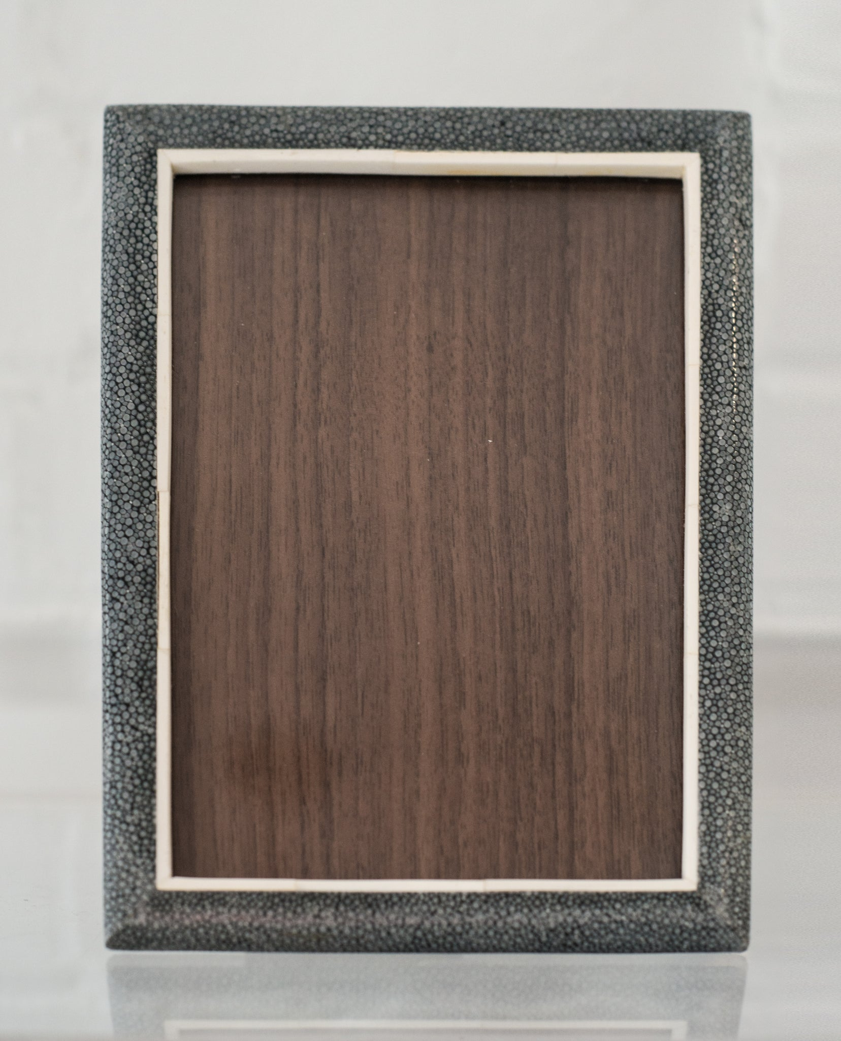 A small picture frame in blue/black Shagreen, bone & walnut, backed in suede.