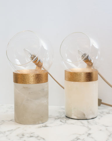 A pair of small lamps on solid quartz bases with glass domes and brass details. Suitable for a desk, night stands or end tables.