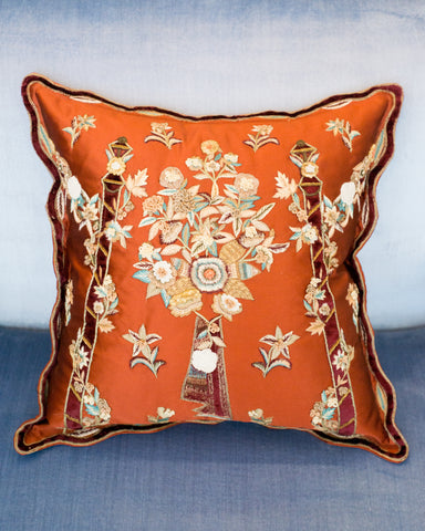 FLORAL METALLIC EMBROIDERY ON A RED SATIN PILLOW