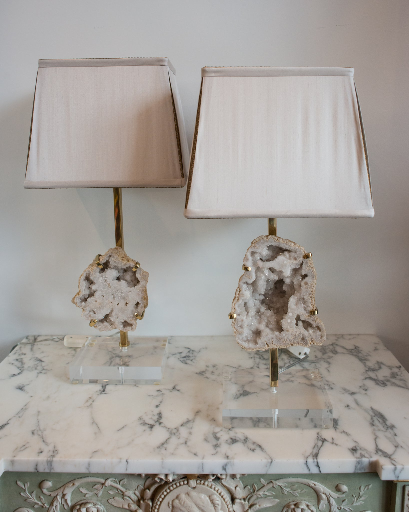Simple yet striking, these lamps contain large sliced quartz stones which are held in place by simple bronze claws resembling a ring setting. These lamps are finished with hand made silk shades with vintage metallic gold trim and sit atop thick acrylic bases. Sold as a pair.