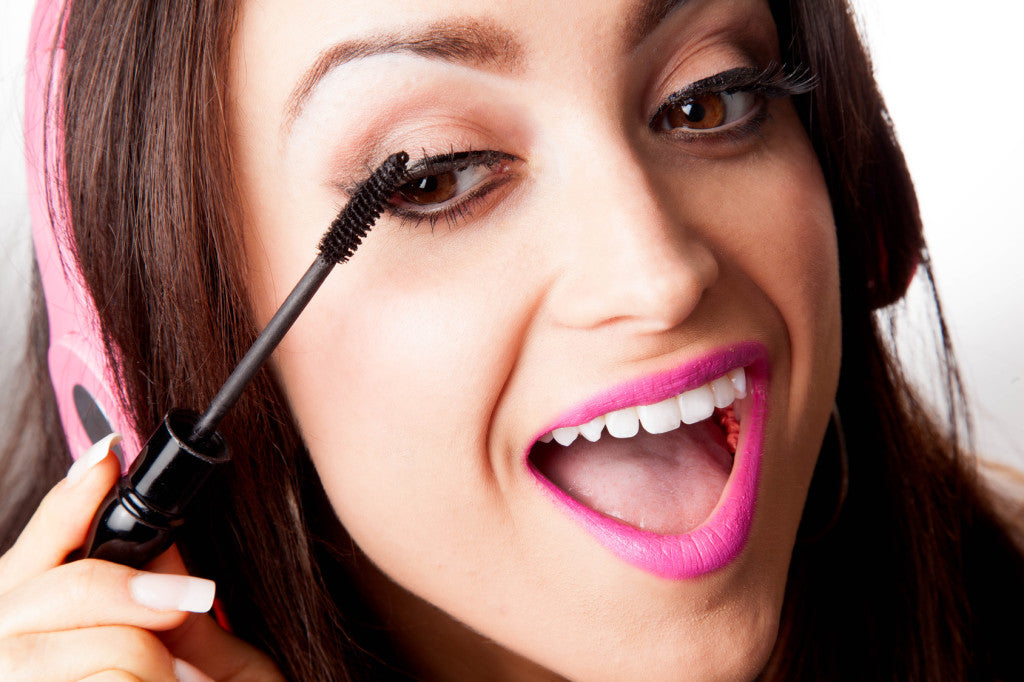 Young Pretty Latino Woman Putting on mascara while listening to Headphones