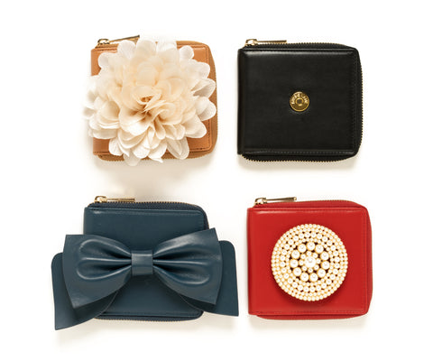 Four Wallets with varying accessories. A brown wallet with a cream flower, a black wallet, a blue wallet with a blue bow, and a red wallet with a pearl accessory.