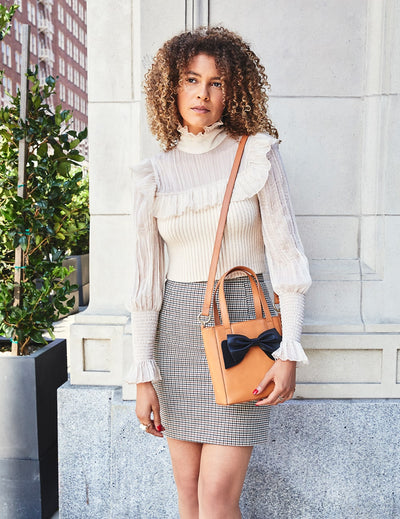 Curly-haired woman wearing an elegant white blouse and a grey skirt, carrying a beige Sonoma mini tote bag, with a black Silverado Bow Acccesory.