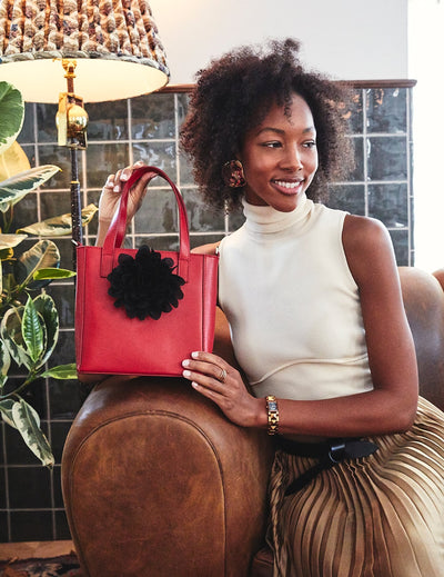 Young, elegant, black woman sitting on a brown leather couch holding a red Sonoma mini tote bag with a black Rutherford flower accessory.