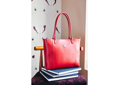 Red leather tote on stack of books.