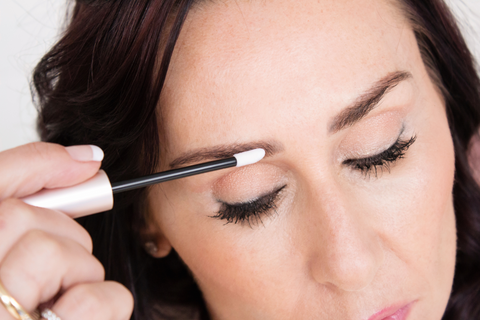Woman applying eyebrow growth serum