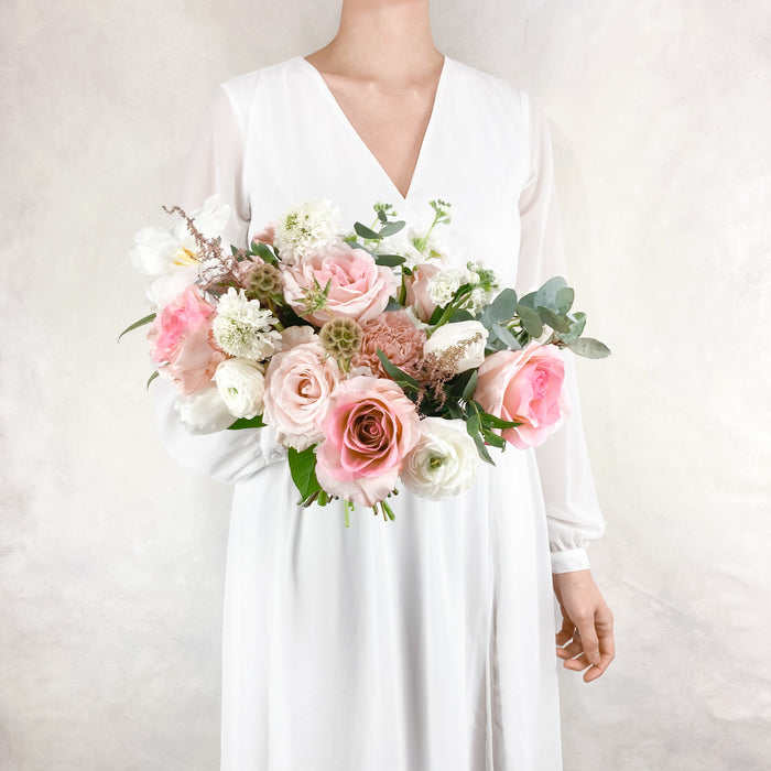 "Our medium sized, lush garden-style bouquet for all of our favorite ladies with all the velvety white and soft blush toned seasonal blooms. This bouquet averages around 10-12"" in diameter so for if you're a bride looking for a smaller bouquet, this is for you!"
