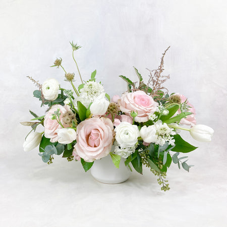 A lush, garden-inspired centerpiece in with lovely white and blush toned blooms. Approximately 12-14 inches in diameter, it is perfect for your 6-10 seat round table or 6-8ft rectangular tables!