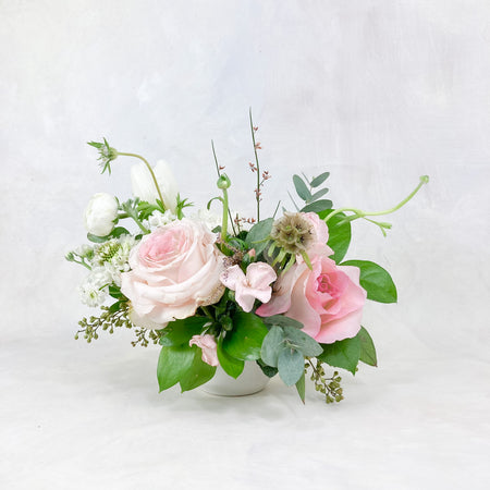 A petite arrangement made with lovely blush and ivory toned blooms. Approximately 6-8 inches in diameter, it is perfect for anywhere you could use an accent of florals - think: high top cocktail tables, in-between the Ella Main Centerpieces to give more dimension and interest to your reception tablescape, guestbook table, cake table, bar etc.
