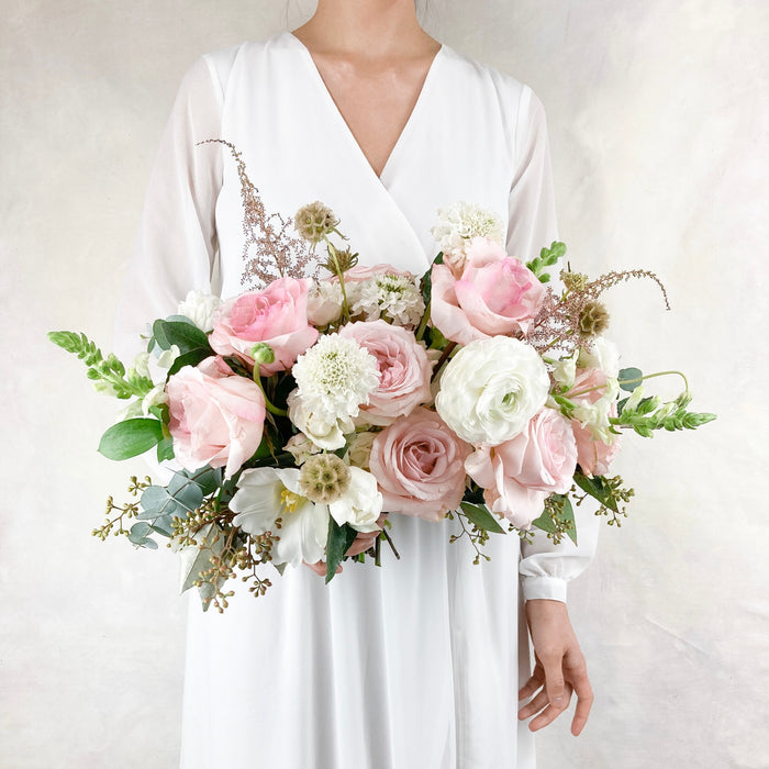 "Our signature lush, loose garden-style bouquet full of soft and romantic blush and white toned blooms. The bridal bouquet averages around 13-15"" in diameter."