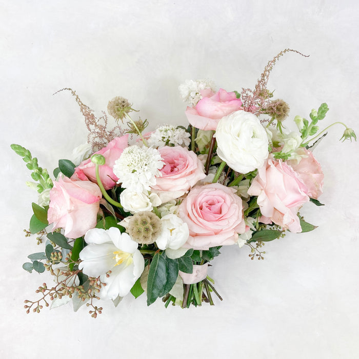 "Our signature lush, loose garden-style bouquet full of soft and romantic blush and white toned blooms. The bridal bouquet averages around 13-15"" in diameter and is finished with a satin ribbon complementing the bouquet."