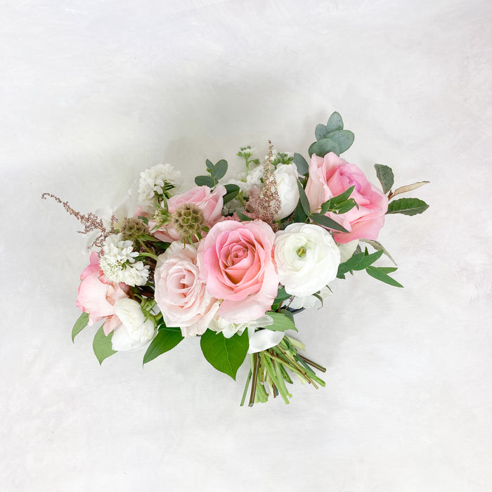 "Our medium sized, lush garden-style bouquet for all of our favorite ladies with all the velvety white and soft blush toned seasonal blooms. This bouquet averages around 10-12"" in diameter and is finished in a satin ribbon complementing the bouquet."