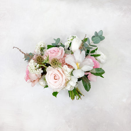 "Our perfectly gathered petite bouquet with luscious blush and cream toned blooms. This bouquet averages around 6-8"" in diameter and is finished in a satin ribbon complementing the bouquet."