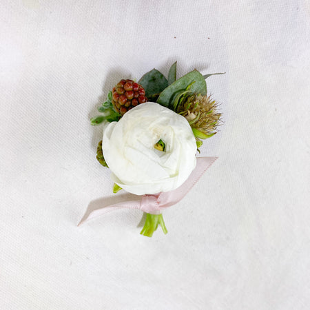 Sweet little boutonnières created with small blush and pink seasonal blooms and greenery accents. Finished with a coordinating satin ribbon + includes 2 bout pins!