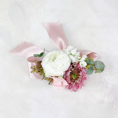 Precious corsages with blush and cream blooms, greenery textures and satin ribbon details. Our wrist corsages will be made in a stretchy bracelet with adjustable ribbons and our pin-on corsages will include two pins to be secured beautifully on a dress or jacket!