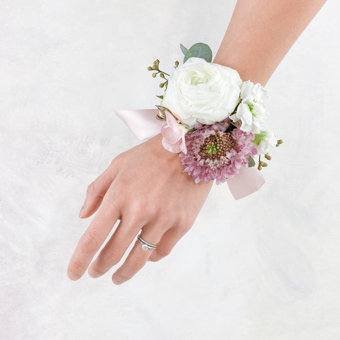 Our beautiful wrist corsage made with seasonal, ivory and blush toned blooms.