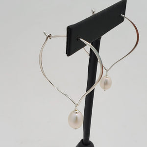 Lotus petal shaped sterling silver hoop earrings with fresh water pearl dangles. Shown on earring display.