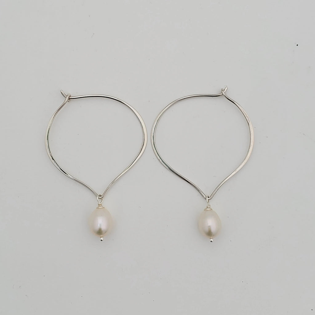 Lotus petal shaped sterling silver hoop earrings with fresh water pearl dangles. Shown laying down.