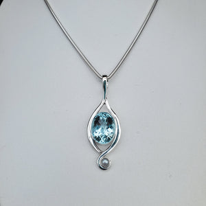 Faceted oval aquamarine gemstone necklace with sterling silver wire accent on both sides and a small fresh water pearl at the bottom.